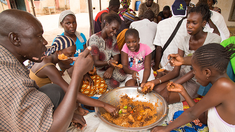 A family gathered around a pot of cowpea stew in Senegal.